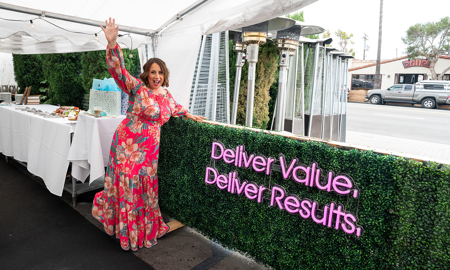 Bree Hughes Stands in front of a Deliver Value Deliver Results sign in San Clemente CA 2021